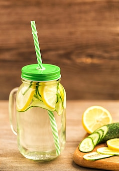 Detox water with cucumbers and orange in a glass jar with a handle, lid and a tube