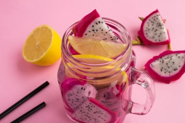 ピンクの背景にドラゴンフルーツとレモンのデトックス水。クローズアップ。