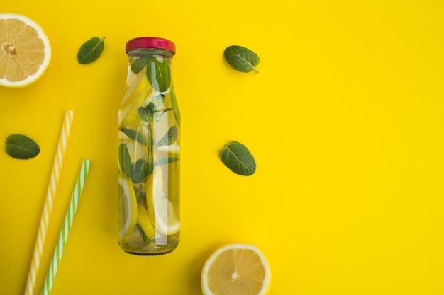 黄色の背景のガラス瓶にレモンとミントを入れた水をデトックスします。上面図。コピースペース。