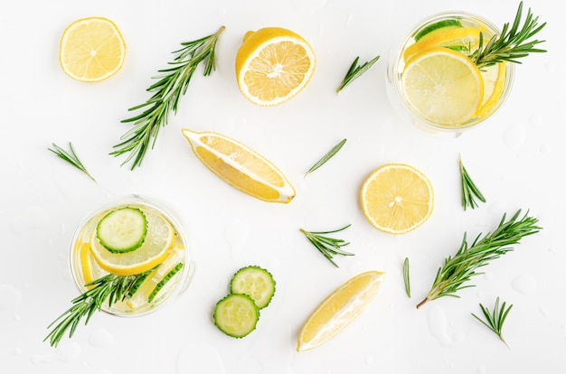 Detox water with lemon, cucumber and rosemary on white background