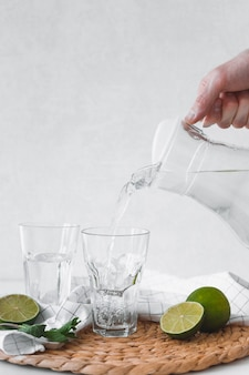 Detox water with lime fruit. hand pouring lime fruit water from jug into glasses.