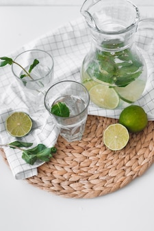 Detox water with lime fruit and mint leaves in jar and glasses