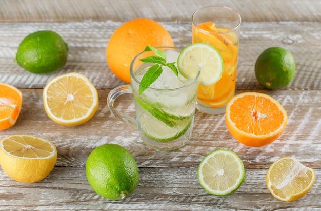 ライム、レモン、オレンジ、ミントカップとガラスの木製の表面、高角度のビューで水をデトックスします。