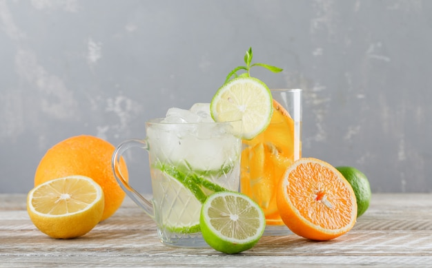 ライム、レモン、オレンジ、ミントのカップと木製のテーブル、側面にガラスのデトックス水。