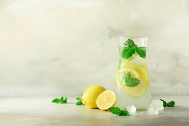 Detox water with mint, lemon on grey background. banner with copy space, sunlight bokeh.