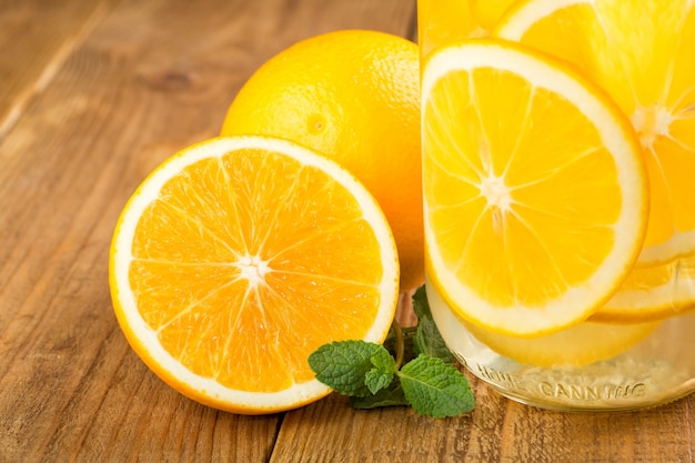 Detox water with orange slices in a glass jar close-up