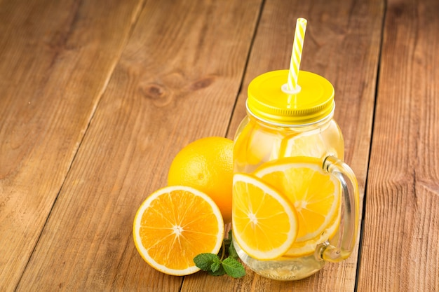 Detox water with orange slices in a glass jar with a handle, lid and straw
