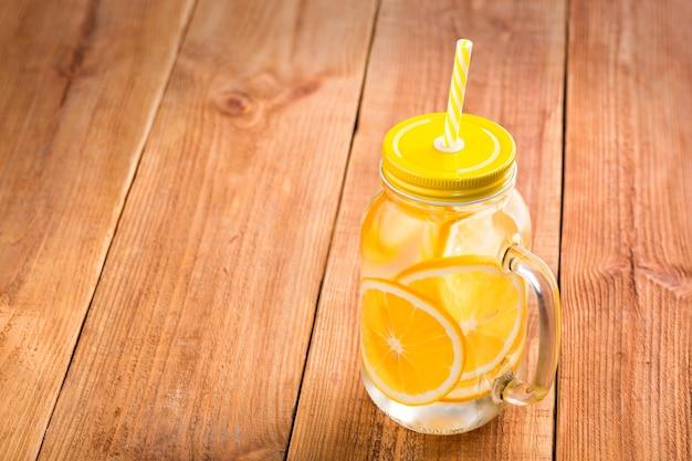 ハンドル、蓋、ストローが付いているガラスの瓶にオレンジスライスで水をデトックス