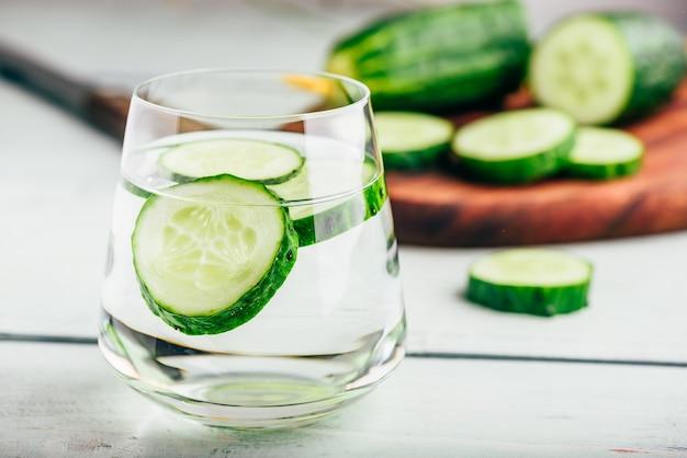 グラスにスライスしたキュウリを入れたデトックス水