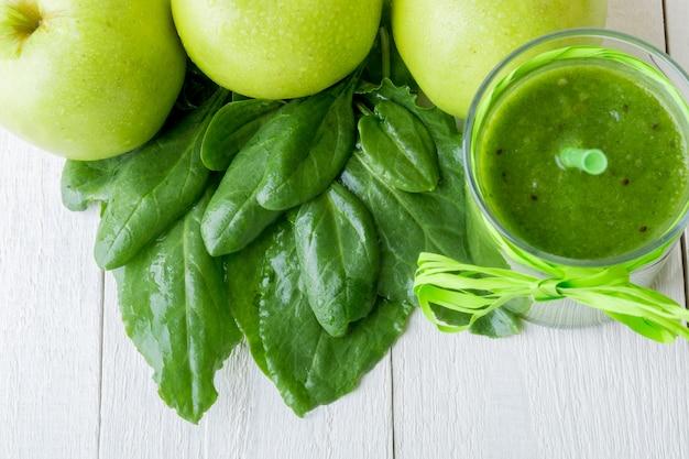 Зеленый коктейль возле ингредиенты для него на белом фоне деревянные. яблоко, лайм, шпинат. detox. здоровый напиток.