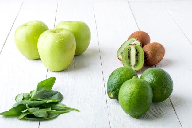 Ингредиенты для смузи. зеленые фрукты на белом фоне деревянные. яблоко, лайм, шпинат, киви. detox. здоровая пища.