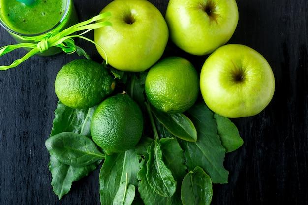 Зеленый коктейль возле ингредиенты для него на черном фоне, деревянные. яблоко, лайм, шпинат. detox. здоровый напиток.