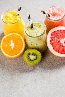 Органические диетические напитки detox, домашние тропические смузи, киви, апельсин, грейпфрут, в порционных баночках, с ингредиентами, на сером каменном столе.