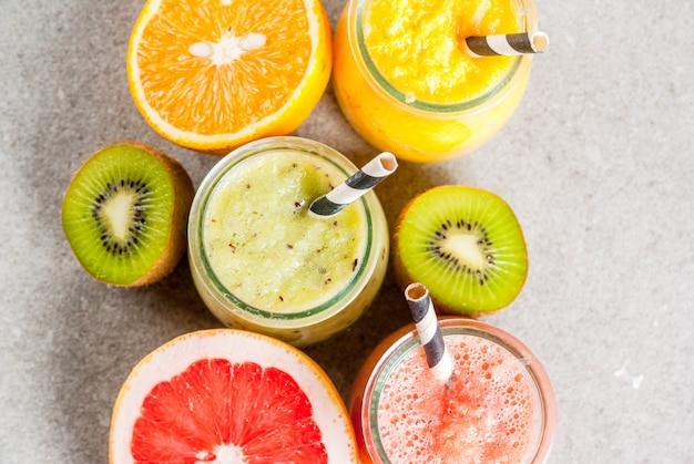 Органические диетические напитки detox, домашние тропические смузи, киви, апельсин, грейпфрут, в порционных баночках, с ингредиентами, на сером каменном столе. вид сверху