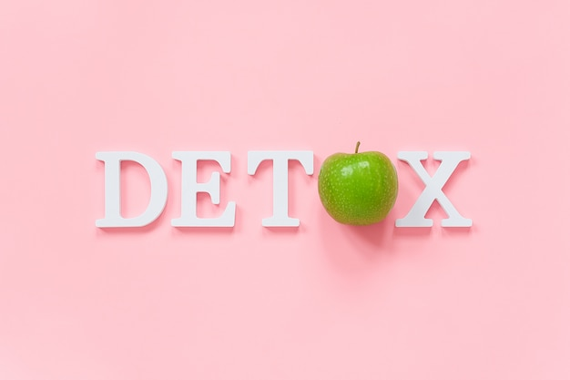 Детоксикация организма и концепция здорового питания. зеленое натуральное свежее яблоко в слове detox из белых букв