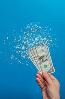 Девальвация денег. печатание денег приводит к инфляции. снижение стоимости американской валюты, доллара. долларовая банкнота распадается на частицы на синем фоне