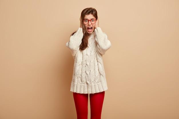 황폐해진 괴로워하는 여성은 귀와 소리를 가리고 화를 내고 짜증을 내며 입을 크게 벌리고 있습니다.