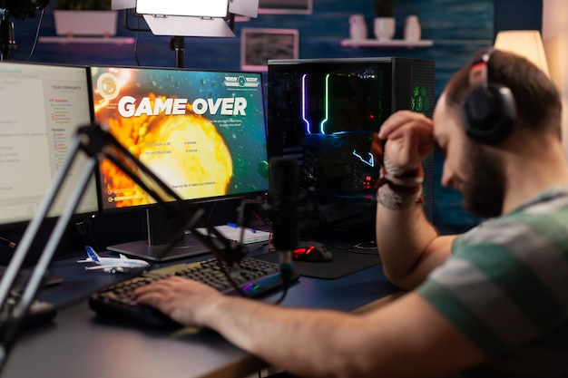 Streamer devastato che indossa le cuffie discute con altri giocatori mentre gioca a sparatutto spaziale. giocatore professionista in streaming di videogiochi online utilizzando microfono e cuffie professionali