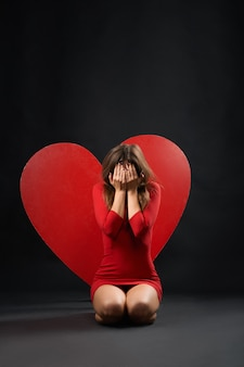 Devastated woman crying red heart