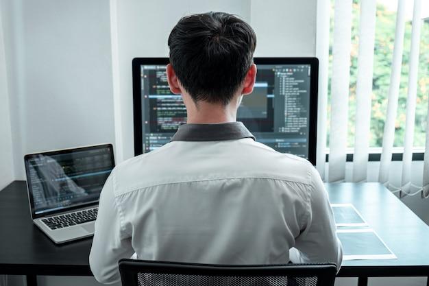 Программист-разработчик, работающий над компьютерным программным обеспечением кодирования в офисе