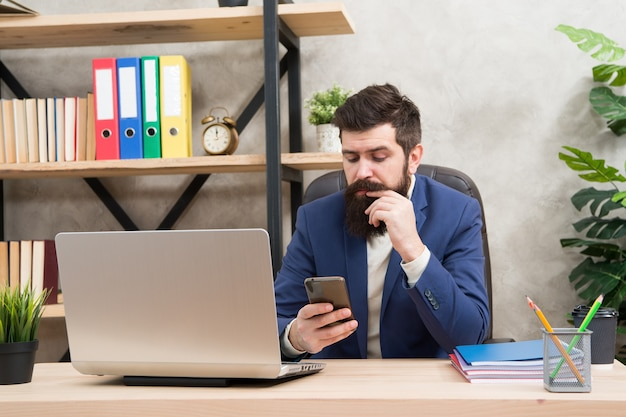 Разработка бизнес-стратегии. рискованное дело. сидеть в интернете. человек бородатый босс-менеджер сидит в офисе с ноутбуком. менеджер, решающий бизнес-задачи. бизнесмен отвечает за успешные бизнес-решения.