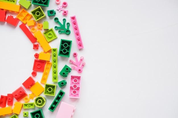 子供向けゲームフレームの開発。白い背景、上面図、テキスト用のスペースにカラフルなプラスチック製のレンガとブロック。子供のための教育玩具。