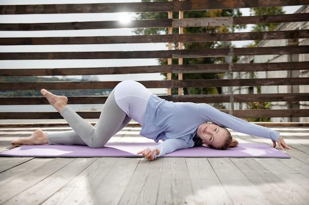 柔軟性の開発。ねじれたヨガの練習を屋外でやっている若い女性