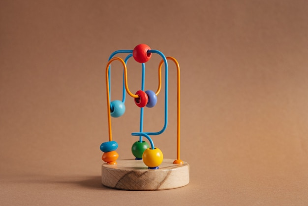 Developing toy for kids the labyrinth of wooden beads on brown background
