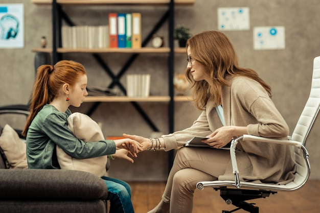 Developing trust. nice friendly woman holding a girls hand while developing trust with her