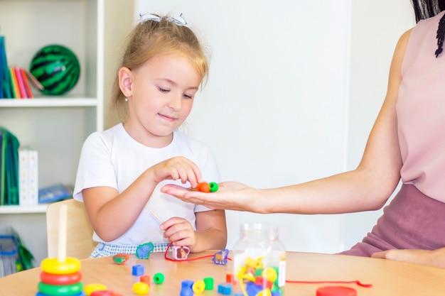 女児との発達および言語療法のクラス。言語療法の練習とビーズを使ったゲーム。女の子は彼女の手にビーズを持っています