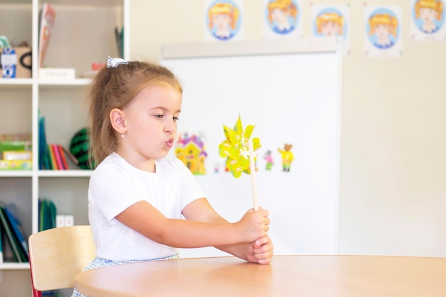 Developmental and speech therapy classes with a child-girl. speech therapy and spinning games. girl blowing