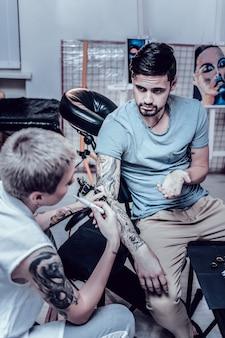 흡연 장치. 문신 살롱의 검은 머리 고객이 부주의 한 흡연 마스터에 의해 혼란스러워합니다.
