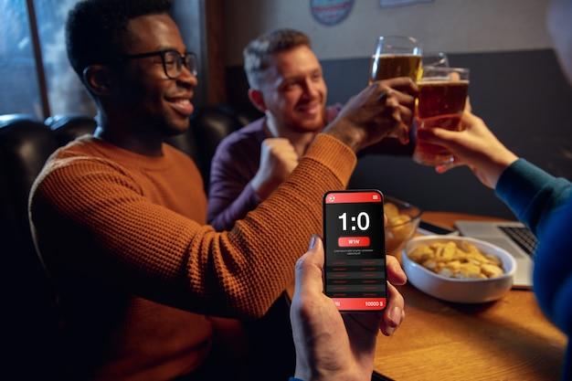 賭けとスコアのためのモバイルアプリを備えたデバイス画面。画面に試合結果が表示され、試合中にバックグラウンドでファンが興奮しているデバイス。