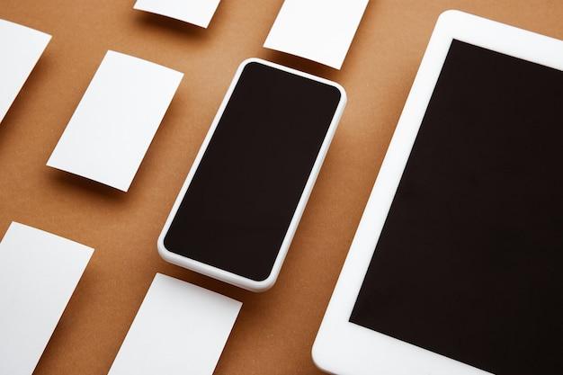 茶色の背景の上に浮かんでいる空白の画面を持つデバイス。電話、タブレット、カード。広告用のオフィススタイルのモダンなモックアップ。デザイン、ビジネス、財務のコンセプトのための空白の白いコピースペース。
