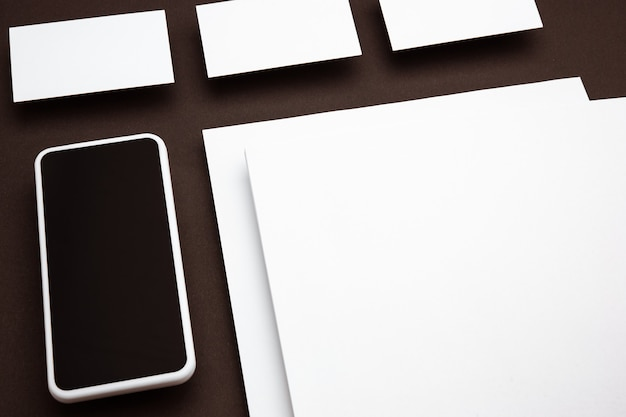 Device with blank screen floating above brown background. phone and cards. office styled, modern mockup for advertising, image or text. blank white copyspace for design, business and finance concept.