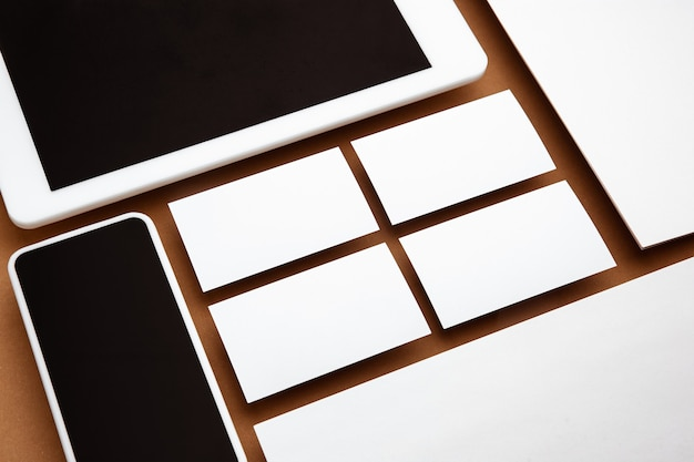 Device with blank screen floating above brown background. phone, tablet and cards. office styled, modern mockup for advertising. blank white copyspace for design, business and finance concept.
