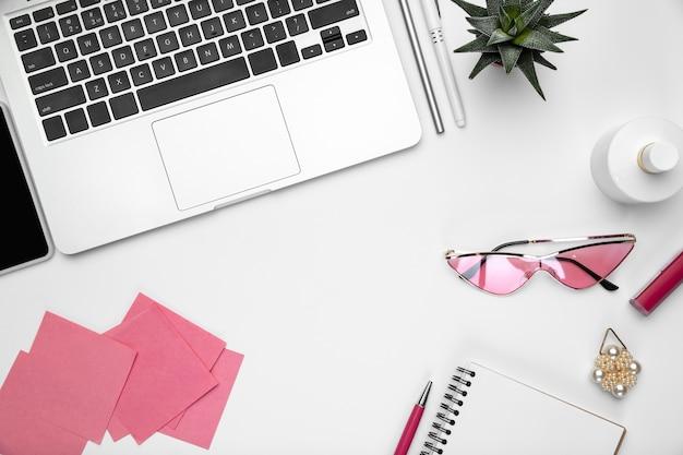 Dispositivi, occhiali. lay piatto, mock-up. area di lavoro femminile dell'ufficio domestico, copyspace. posto di lavoro stimolante per la produttività. concetto di affari, moda, freelance, finanza, opere d'arte colori pastello alla moda