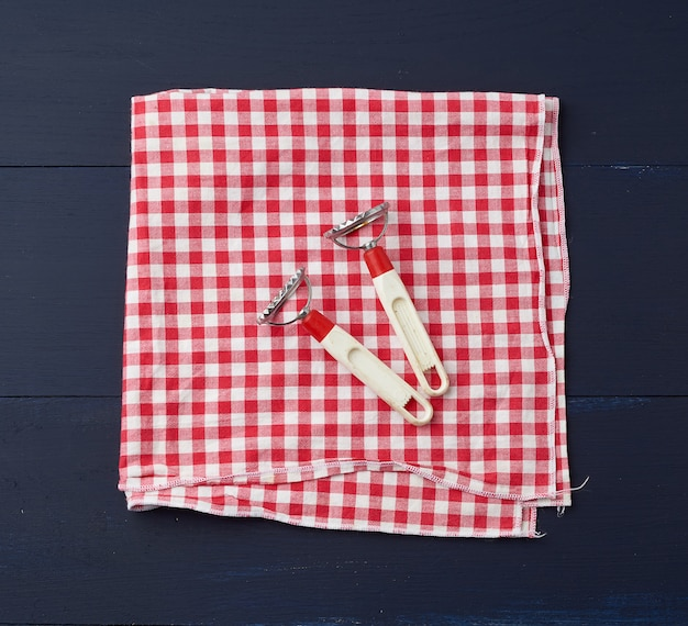 Devices for making ravioli on red and white textile kitchen napkin