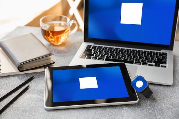 광고용 카피스페이스가 있는 장치 또는 가제트 - 모형, 디지털 개념. 노트북, 시계, 상위 뷰가 있는 고도의 디지털 작업 공간이 있는 사무실 또는 공동 작업 위치. 온라인 작업, 쇼핑, 서비스 개념입니다.