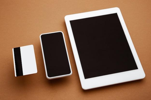 茶色の背景の上に浮かぶ空白の画面を持つデバイス電話タブレットカード