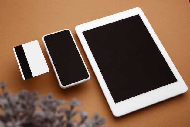 Devices with blank screens floating above brown background phone tablet office styled mockup