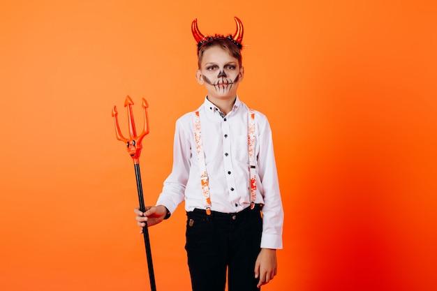 Devil boy standing against an orange  in masquerade makeup. halloween