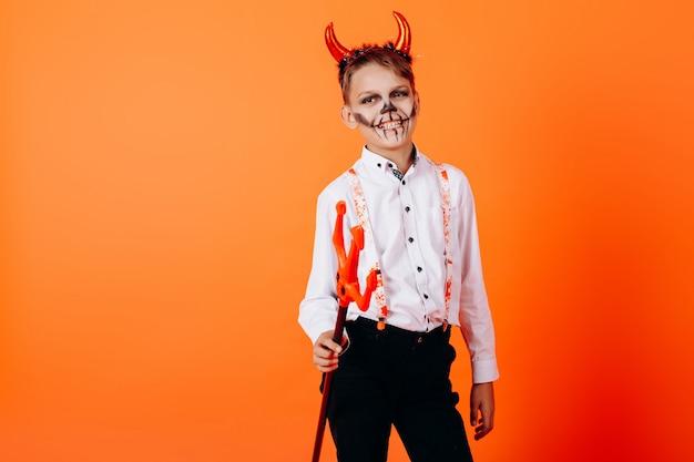 Devil boy standing halfturn against an orange  in masquerade makeup. halloween