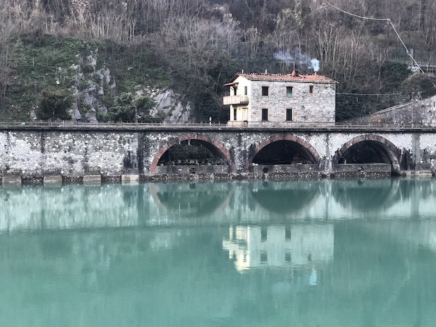 Devil bridge surrounded by hills covered in greenery and houses reflecting on the water in italy