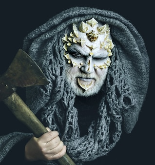 Дьявольское существо с кожей дракона и бородой, человек с топором в руке, голова демона с серым капюшоном на лице черного монстра с белыми глазами, шипами и бородавками, концепция ужаса и смерти