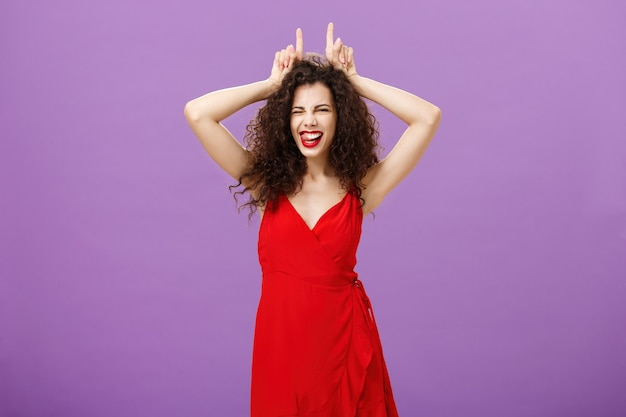 Devil lives inside lady. daring stylish adult woman with curly hairstyle in red evening dress winking making confident and amused expression showing horns with index fingers on head, being stubborn.