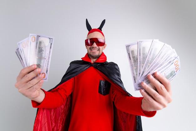 彼の手にたくさんのお金を示すハロウィーンの衣装を着た悪魔の男