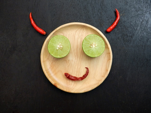 Devil smile, wooden plate is face, lemon slice is eye, red dry chili is mouth and red chil