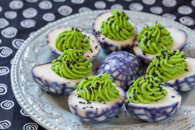 Deviled egg with avocado with spider web pattern topped black sesame