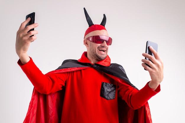 白いスタジオの上に彼の手で2つのスマートフォンで銃を持っている仮面舞踏会のお祝いの黒赤の衣装を着た悪魔の男。